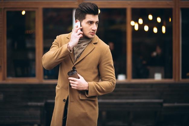 Giovane in cappotto fuori parlando al telefono e bere caffè