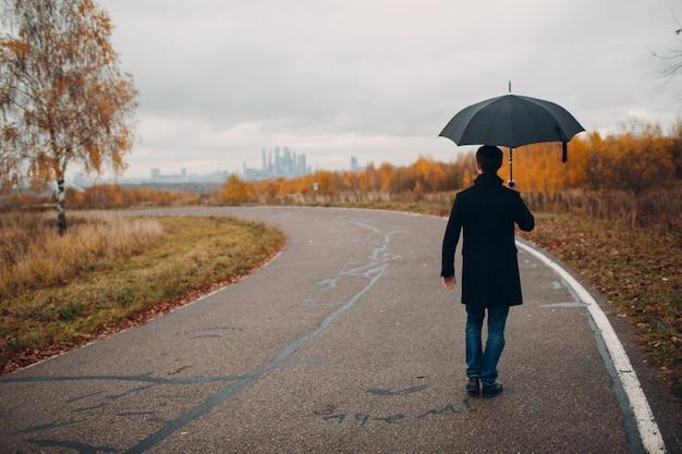 Giovane in cappotto nero che cammina sotto la pioggia con l'ombrello