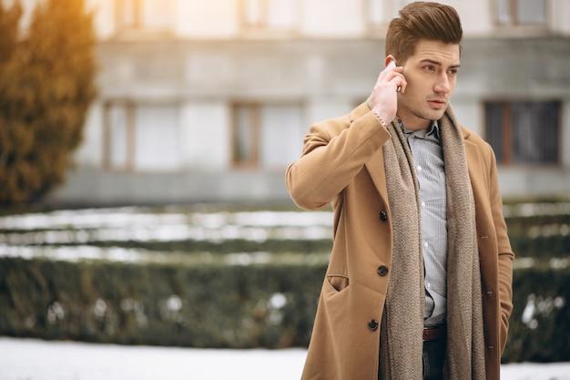 Giovane in cappotto parlando al telefono all'esterno