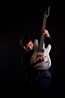 Giovane in giacca di pelle nera con chitarra elettrica