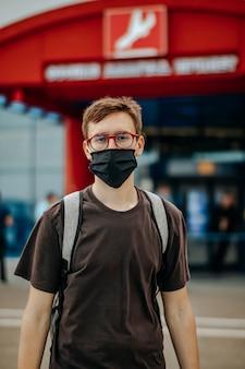Giovane in maglietta nera, maschera chirurgica, occhiali, zaino guardando la telecamera. aeroporto sullo sfondo