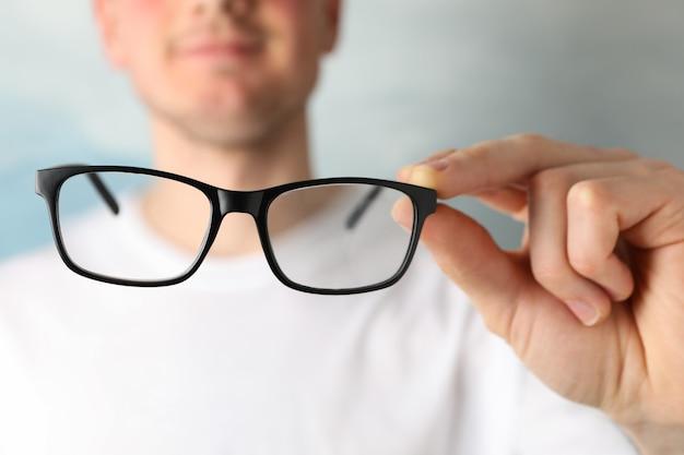 Giovane in maglietta tenere occhiali, da vicino