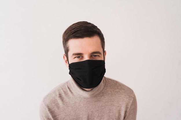 Giovane in una maschera protettiva nera. dispositivi di protezione individuale per coronovirus. maschera fatta in casa per l'accesso a luoghi pubblici