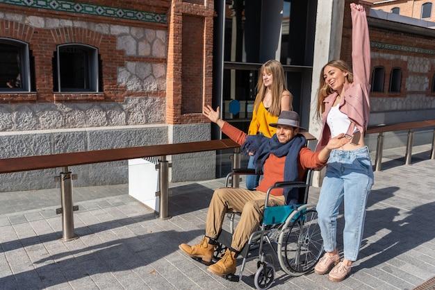 Giovane in una sedia a rotelle accanto a due ragazze felici che camminano per la strada