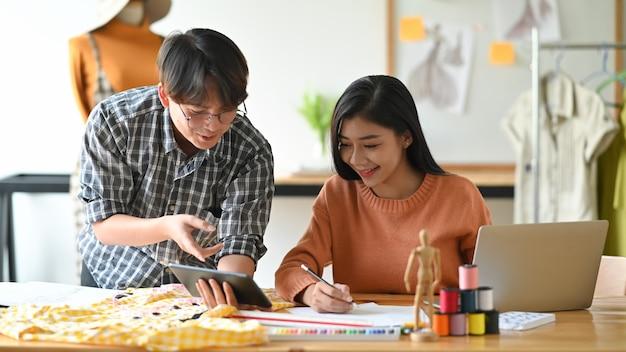Giovane incontro alla moda con l'abbozzo dello stilista e pianificazione con la tavoletta digitale.