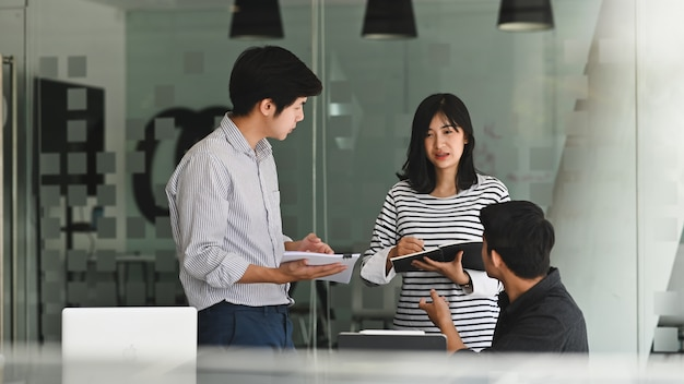 Giovane incontro di lavoro con un progetto di avvio in ufficio moderno.