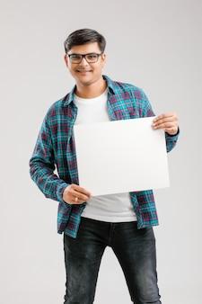 Giovane indiano, asiatico che mostra insegna in bianco