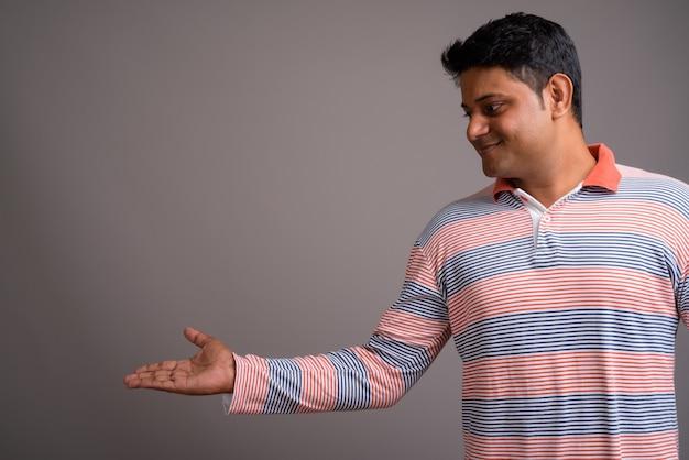 Giovane indiano che indossa la camicia di polo a righe a maniche lunghe