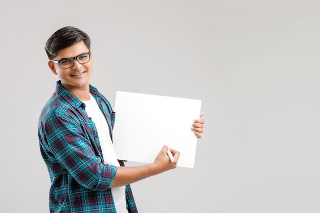 Giovane indiano con gli occhiali e scrivere qualcosa su una lavagna vuota