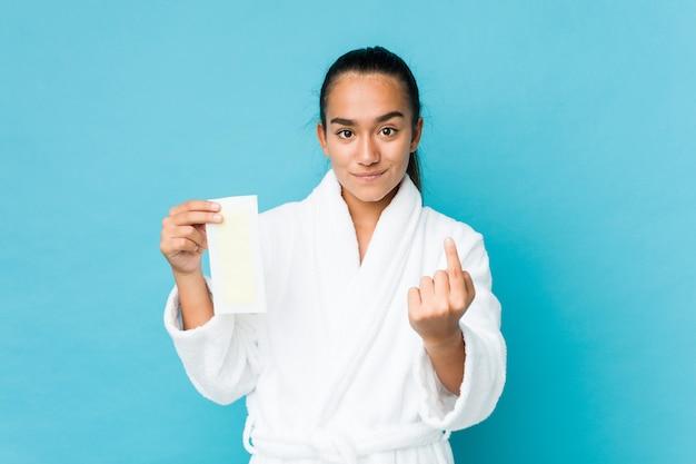 Giovane indiano di razza mista con in mano una fascia depilatoria che punta con il dito contro di te come se l'invito si avvicinasse.