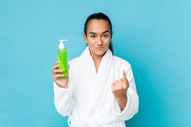 Giovane indiano di razza mista in possesso di una bottiglia di aloe vera che punta con il dito contro di te come se l'invito si avvicina.