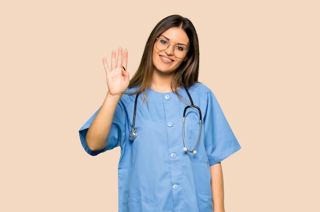 Giovane infermiera che saluta con la mano con l'espressione felice su fondo giallo isolato
