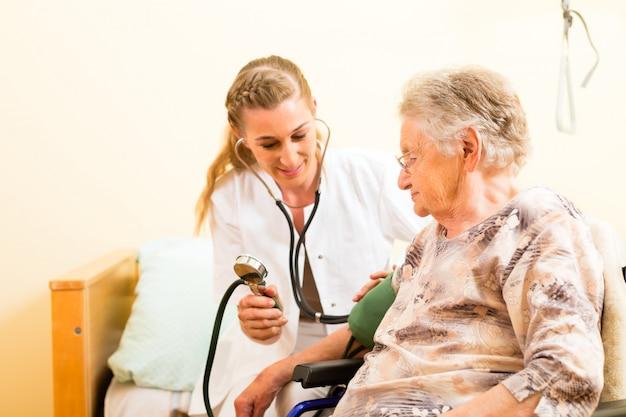 Giovane infermiera e senior femminile in casa di cura