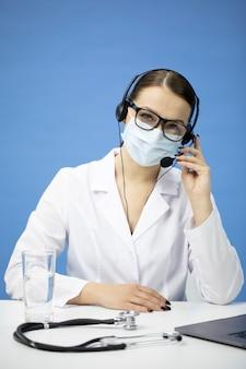 Giovane infermiera femminile in maschera medica con auricolare su consultazione paziente hotline