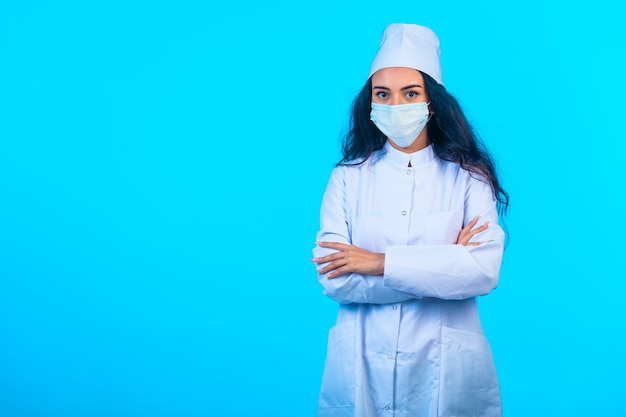 Giovane infermiera in uniforme isolata che tiene le mani di chiusura e sembra sicura di sé