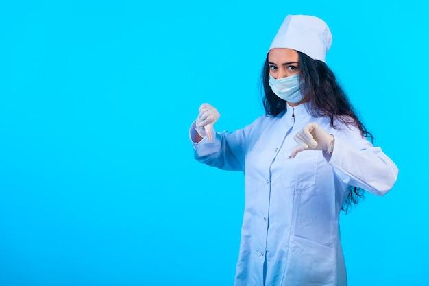 Giovane infermiera nella holding uniforme isolata che fa il pollice giù il segno della mano