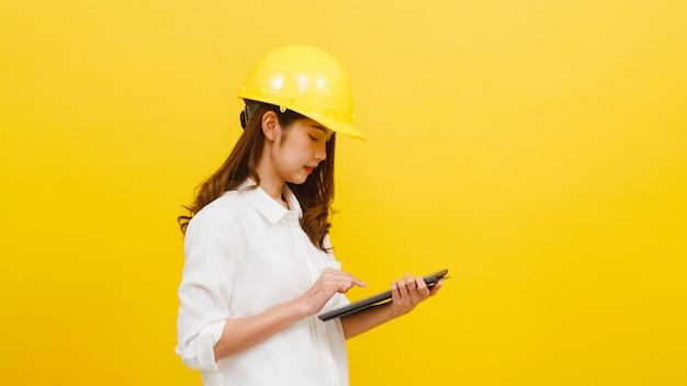 Giovane ingegnere asiatico della donna che per mezzo della compressa digitale con l'espressione positiva, vestita in abbigliamento casual ed esaminando macchina fotografica sopra la parete gialla. la donna felice adorabile felice si rallegra del successo.
