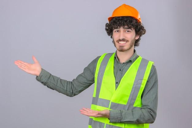 Giovane ingegnere bello barbuto che sorride presentazione allegra e che indica con il palmo della mano che esamina la macchina fotografica sopra la parete bianca isolata