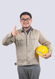 Giovane ingegnere con elmetto giallo e pollice in alto