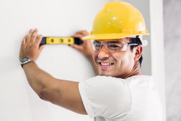 Giovane ingegnere di costruzione in un casco giallo che lavora e che effettua le misure sulla parete al cantiere della costruzione