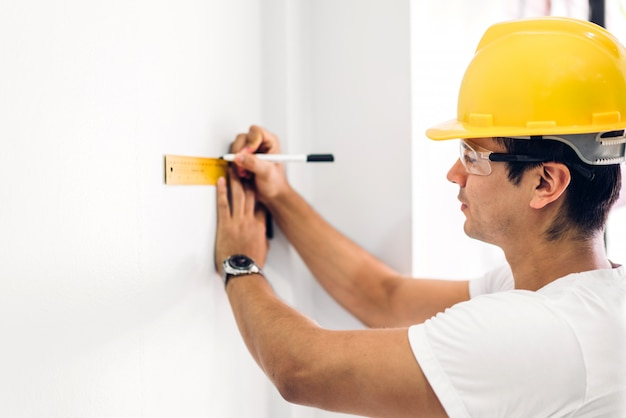 Giovane ingegnere di costruzione in un casco giallo che lavora e che guarda lavoro per il progetto di pianificazione al sito della casa della costruzione