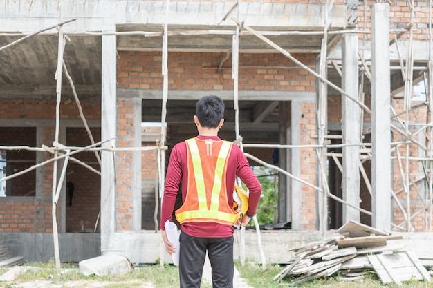Giovane ingegnere di fronte a una casa incompiuta.