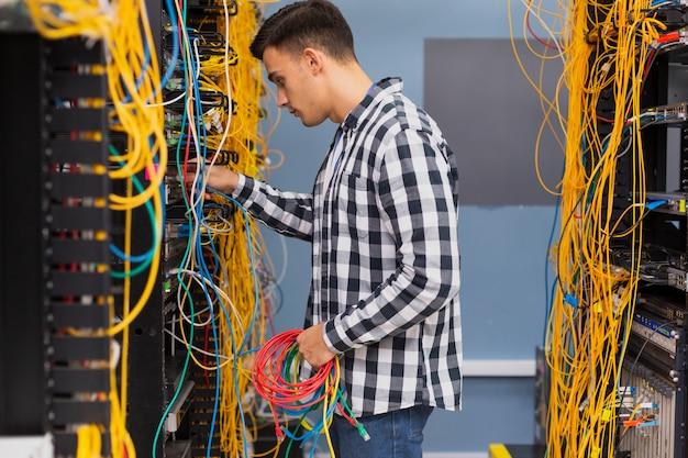 Giovane ingegnere di rete con fili ethernet a tiro medio
