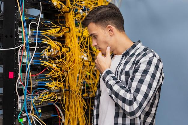 Giovane ingegnere di rete sul colpo medio della stanza del server