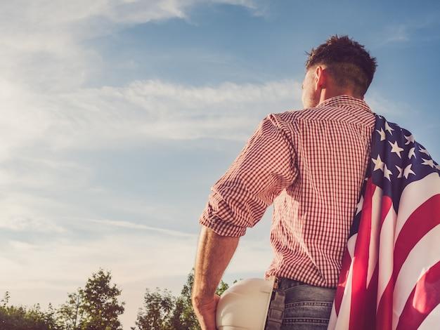 Giovane ingegnere, elmetto protettivo bianco e bandiera americana