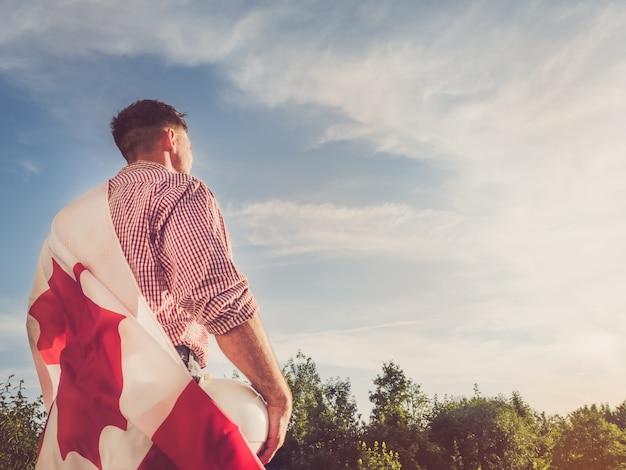 Giovane ingegnere, elmetto protettivo bianco e bandiera canadese