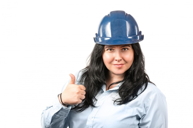Giovane ingegnere o architetto sorridente attraente della donna del brunette con il cappello di sicurezza blu che mostra i pollici in su