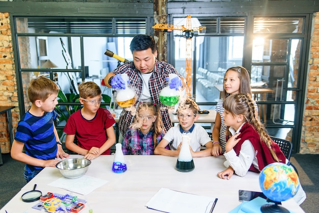 Giovane insegnante asiatico con un gruppo di sei allievi caucasici allegri di 8-10 anni che indossano gli occhiali protettivi durante l'esperimento chimico con liquidi colorati nella scuola moderna.