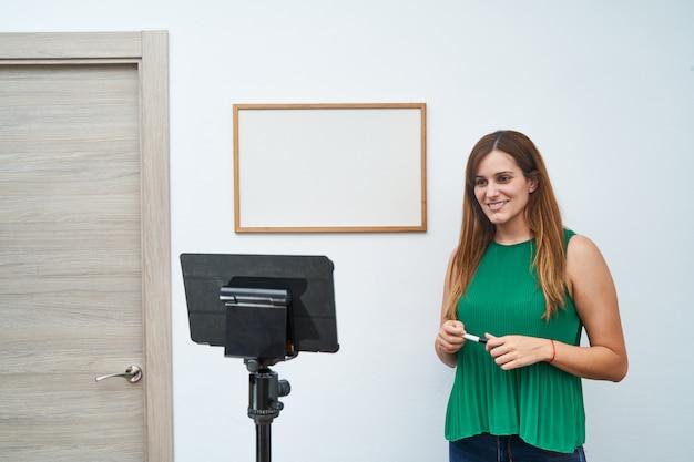 Giovane insegnante che dà lezioni online a casa tramite videochiamata. concetto di nuove tecnologie, studio e lezioni online.