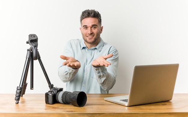 Giovane insegnante di fotografia bello che tiene qualcosa con le palme, offrendo alla fotocamera.