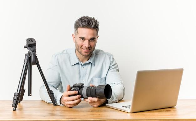 Giovane insegnante di fotografia bello felice, sorridente e allegro.