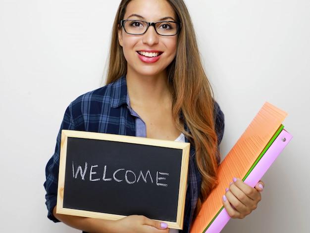 Giovane insegnante femminile che tiene cartelle e lavagna
