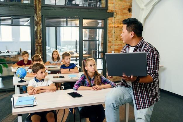 Giovane insegnante maschio coreano che si siede sullo scrittorio con il computer portatile che dà lezione per sei allievi della scuola elementare.