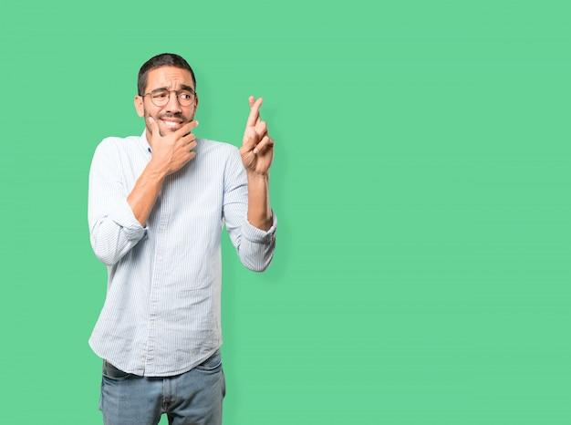 Giovane interessato che fa un gesto incrociato delle dita