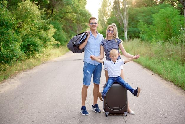 Giovane intoppo del viaggiatore della famiglia che fa un'escursione sulla strada vuota