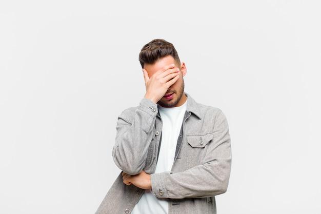 Giovane ispanico che sembra stressato, imbarazzato o turbato, con un mal di testa, che copre il viso con la mano contro il muro grigio