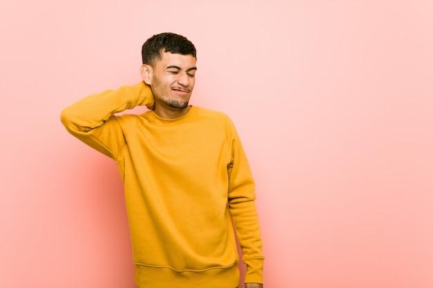 Giovane ispanico che soffre di dolore al collo a causa dello stile di vita sedentario.