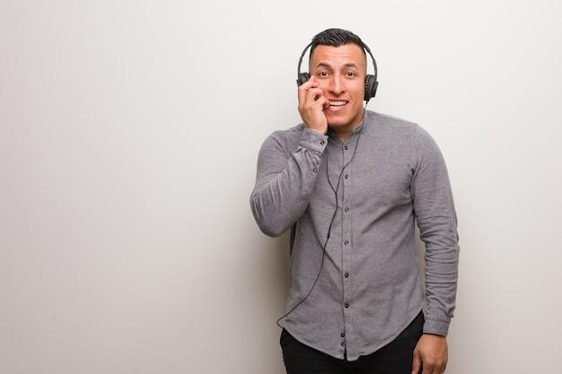 Giovane latino che ascolta la musica che morde le unghie, nervoso e molto ansioso