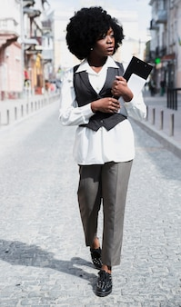 Giovane lavagna per appunti della tenuta della donna di affari e compressa digitale a disposizione che camminano sulla strada