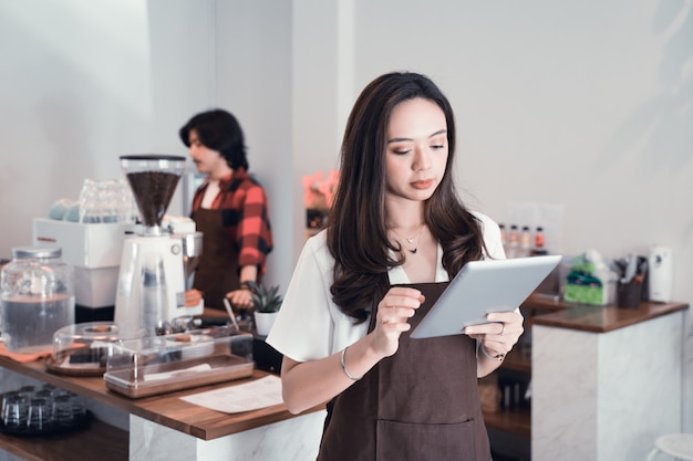 Giovane lavoratore asiatico del caffè con la compressa.