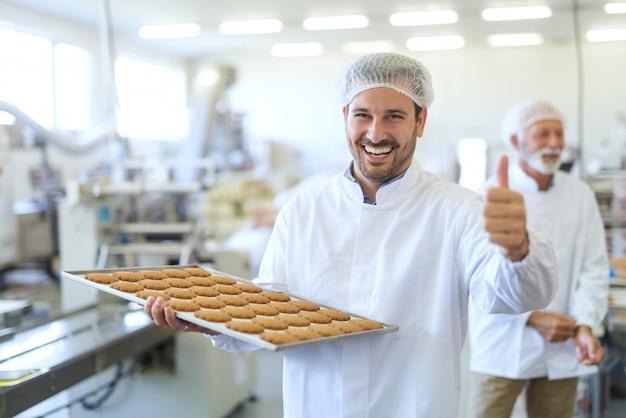 Giovane lavoratore caucasico in abbigliamento da lavoro tenendo il vassoio con i biscotti e dando il pollice in alto mentre si trovava nella fabbrica di cibo.