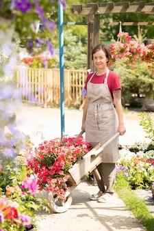 Giovane lavoratore del garden center con carrello in piedi sul corridoio tra le aiuole mentre lavora in serra