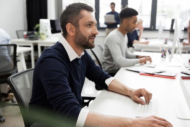 Giovane lavoratore maschio che si siede e che lavora al suo computer