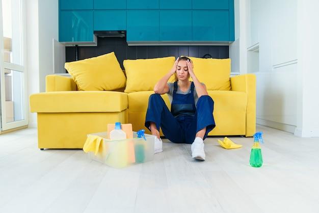 Giovane lavoratrice del servizio di pulizia che si siede vicino allo strato e che si sente stanca dopo avere lavato il pavimento sulla cucina.