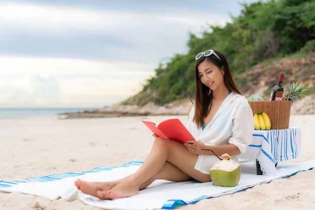 Giovane lettura asiatica della donna sulla spiaggia