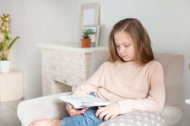 Giovane libro di lettura della ragazza dell'adolescente a casa. istruzione a distanza, educazione domestica. concetto di autoisolamento